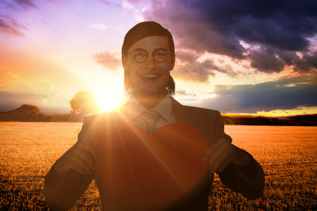 Geeky businessman smiling and holding heart card  against countryside scene Stock Photo