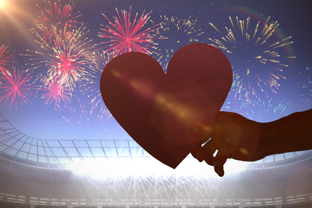 Heart against fireworks exploding over football stadium Stock Photo