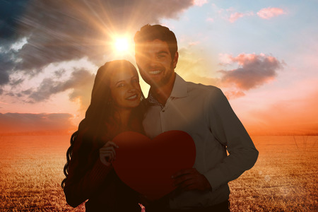 Happy couple holding paper heart against sunrise over field Stock Photo