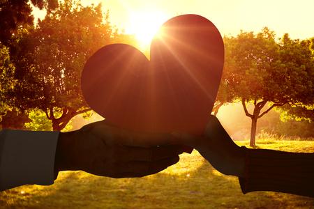 Couple holding heart against sunrise over trees