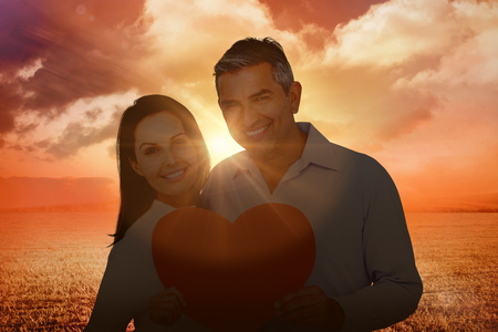 Happy couple holding big heart shape paper against sunrise over field
