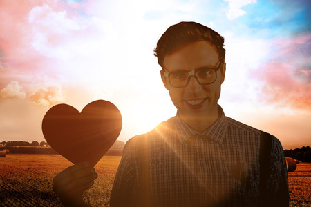 Geeky hipster holding a heart card against countryside scene Stock Photo
