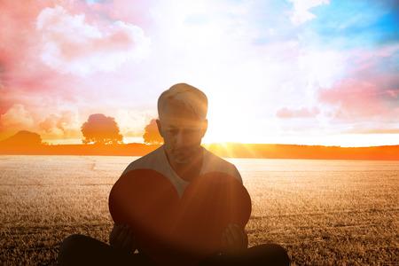 Upset man sitting holding heart shape against countryside scene Stock Photo