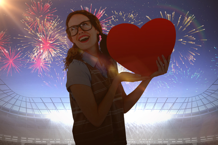 Geeky hipster woman holding heart card against fireworks exploding over football stadium
