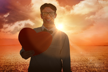 geeky: Geeky hipster holding heart card against sunrise over field Stock Photo