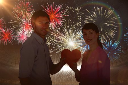 Couple holding a red heart against fireworks exploding over football stadium