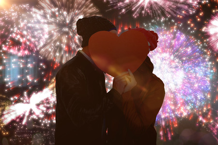 bobble: Happy young couple holding heart shape paper against colourful fireworks exploding on black background Stock Photo