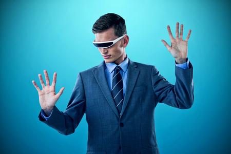 imagining: Businessman imagining while using virtual reality glasses against blue vignette background