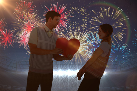 big shirt: Geeky hipster giving heart card to his girlfriend  against fireworks exploding over football stadium