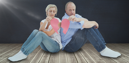 Sad mature couple holding a broken heart against black room