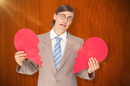 geeky: Geeky businessman crying and holding broken heart card against wooden oak table Stock Photo