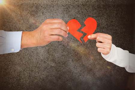 strife: Couple holding broken heart shape paper against close-up of road surface