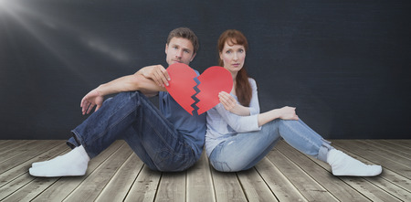 snapped: Couple holding a broken heart against black room
