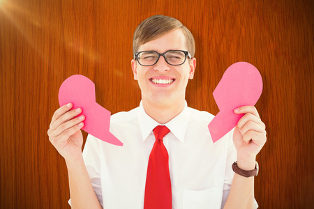 Geeky hipster holding a broken heart card against wooden oak table Stock Photo