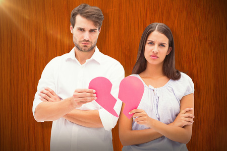 Upset couple holding two halves of broken heart against wooden oak table