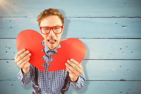 geeky: Geeky hipster holding a broken heart  against painted blue wooden planks