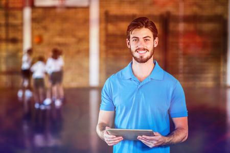 학교 체육관에서 농구 코트에서 디지털 태블릿을 사용하여 스포츠 선생님의 초상화
