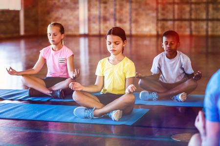 Bambini di scuola che meditano durante la classe di yoga nel campo di pallacanestro nella scuola di palestra Archivio Fotografico - 70084224