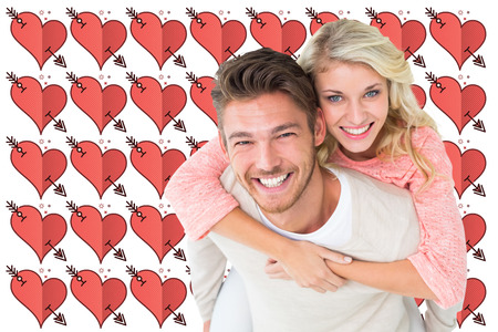 perforated: Handsome man giving piggy back to his girlfriend against perforated heart symbols