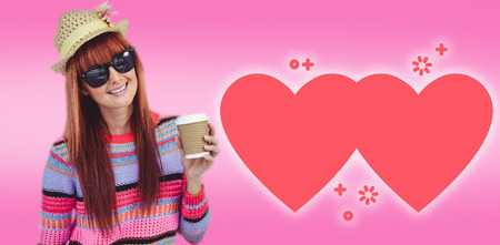 Attractive hipster woman holding a cup of coffee against pink Stock Photo