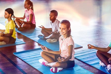 Bambini di scuola che meditano durante la classe di yoga nel campo di pallacanestro nella scuola di palestra Archivio Fotografico - 70084295