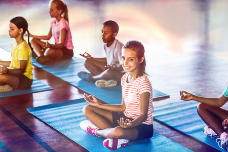 School kids meditating during yoga class in basketball court at school gym Stok Fotoğraf - 70084295