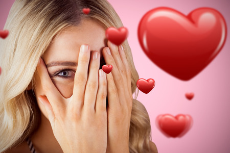 woman hiding: Beautiful blonde woman hiding behind hands against pink background