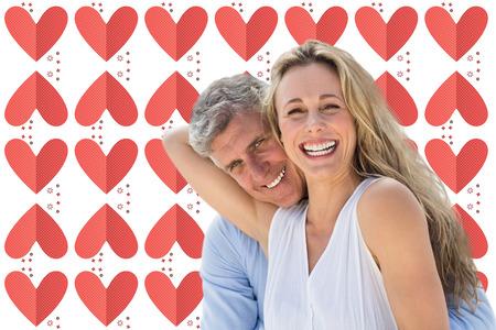 Happy mature couple against pink heart symbols Stock Photo