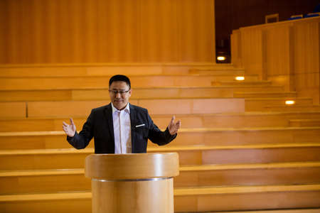 rostrum: Male business executive giving a speech at conference center LANG_EVOIMAGES