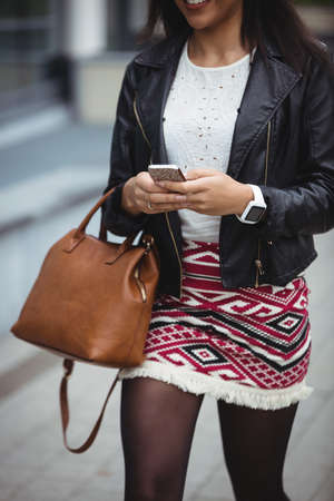 premises: Woman using mobile phone while walking in office premises