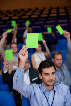 consent: Business executives show their approval by raising hands at conference center LANG_EVOIMAGES