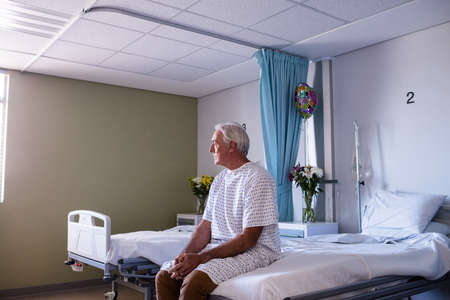 ageing process: Thoughtful male senior patient sitting in the ward at hospital