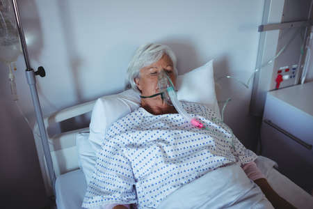 ageing process: Senior patient lying on bed with oxygen mask on face in hospital