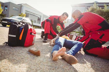 Paramedics examining injured woman on street