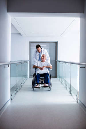 ageing process: Doctor interacting with male senior patient on a wheelchair in the passageway
