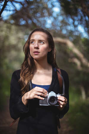 looking away from camera: Beautiful woman standing with camera in forest