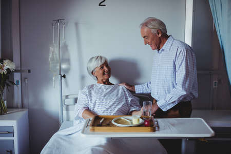 ageing process: Senior woman interacting with senior man in the ward at hospital LANG_EVOIMAGES