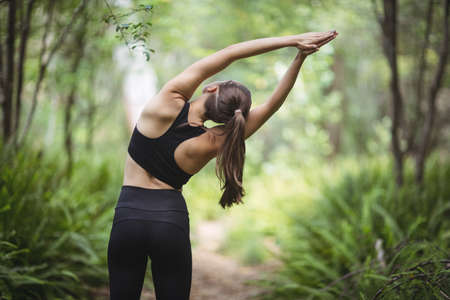 people: Rear view of woman performing stretching exercise in forest