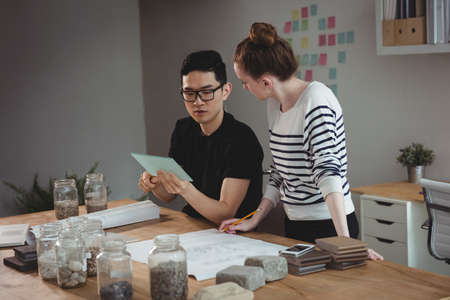 a jar stand: Business executives using digital tablet in office LANG_EVOIMAGES