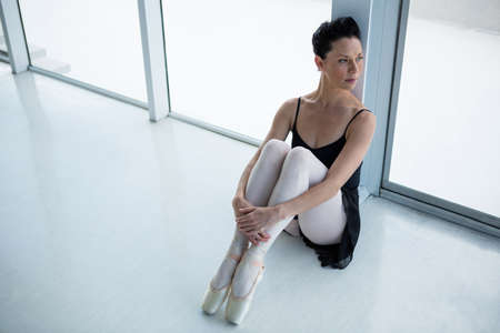 Thoughtful ballerina sitting on floor in the ballet studio
