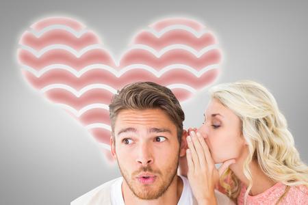 Attractive blonde whispering secret to boyfriend against grey vignette Stock Photo