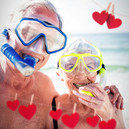 Hearts hanging on a line against happy senior couple with diving masks