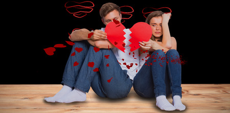 broken love: Young couple holding broken heart against red hearts floating