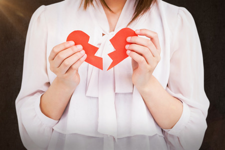 Woman holding broken heart paper against grey background Stock Photo