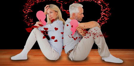 Unhappy couple sitting while holding broken heart against red hearts floating Stock Photo