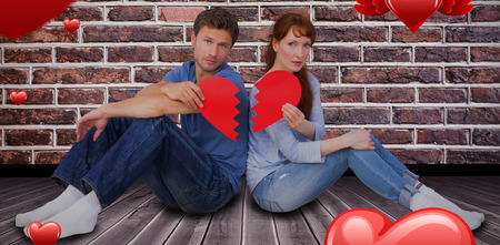 snapped: Couple holding a broken heart against room background 3D Stock Photo