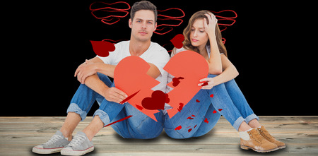 Young couple sitting on floor with broken heart shape paper against red love hearts