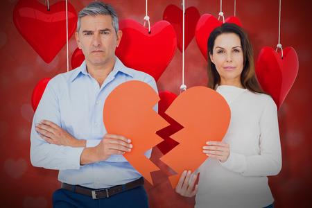strife: Portrait of couple holding broken heart shape paper against valentines heart design 3d