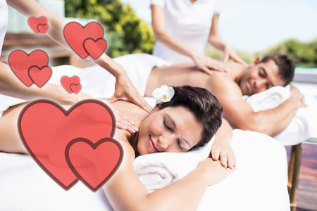 young couple receiving a back massage from masseur Stock Photo