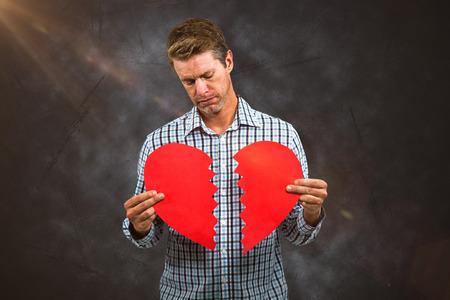 Sad man holding a broken card against grey Stock Photo